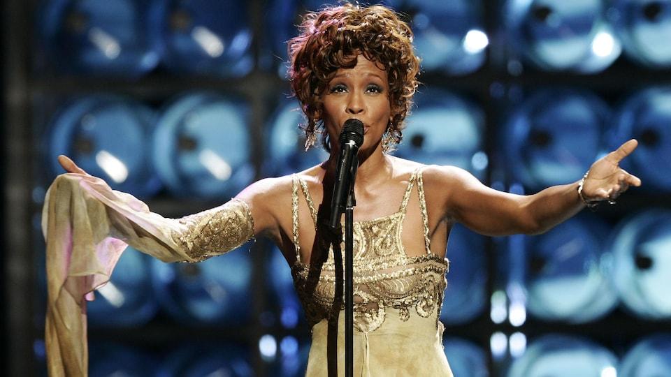 Whitney Houston chante sur une scène.