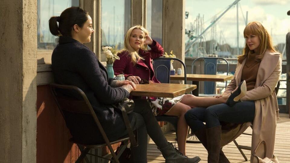 Les trois femmes sont autour de la table d'un café, à l'extérieur.