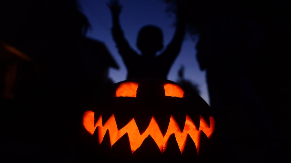 Un enfant lève les bras derrière une citrouille illuminée, la nuit.