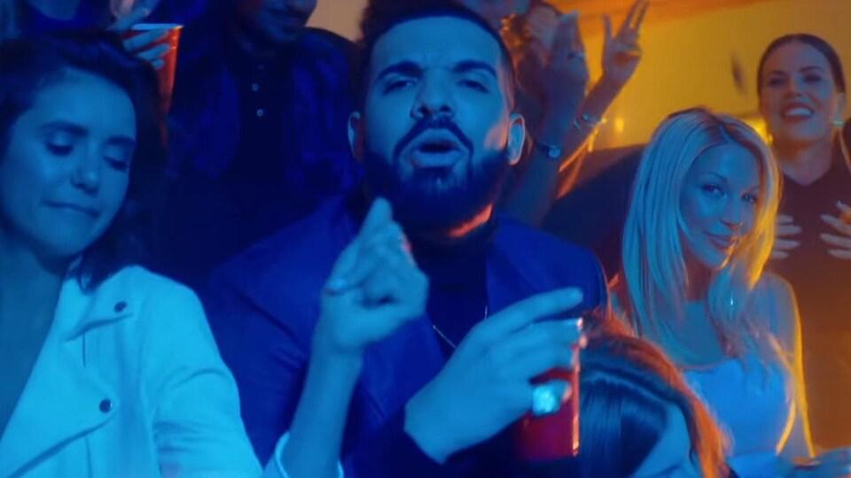 Le chanteur Drake regarde vers la caméra, entouré de jeunes femmes