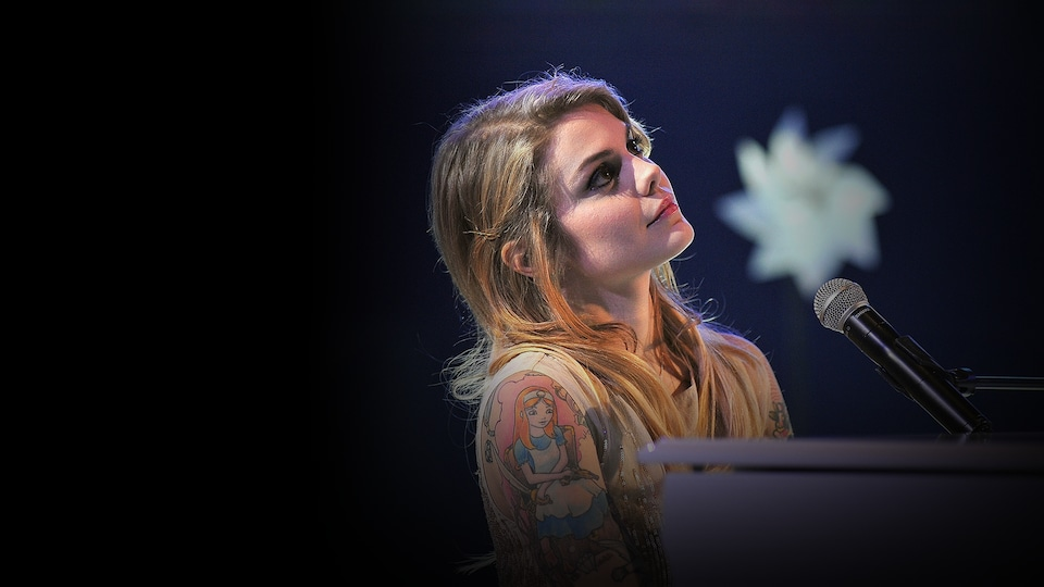 La jeune femme est au piano sur une scène, micro devant elle.