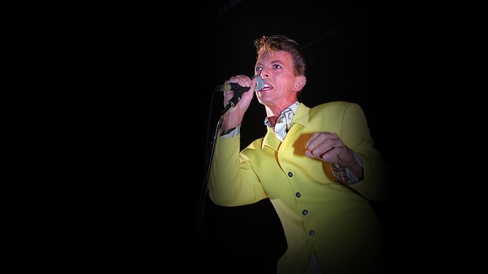 Le chanteur tient un micro devant sa bouche et porte une chemise jaune. Le fond de la photo est noir.