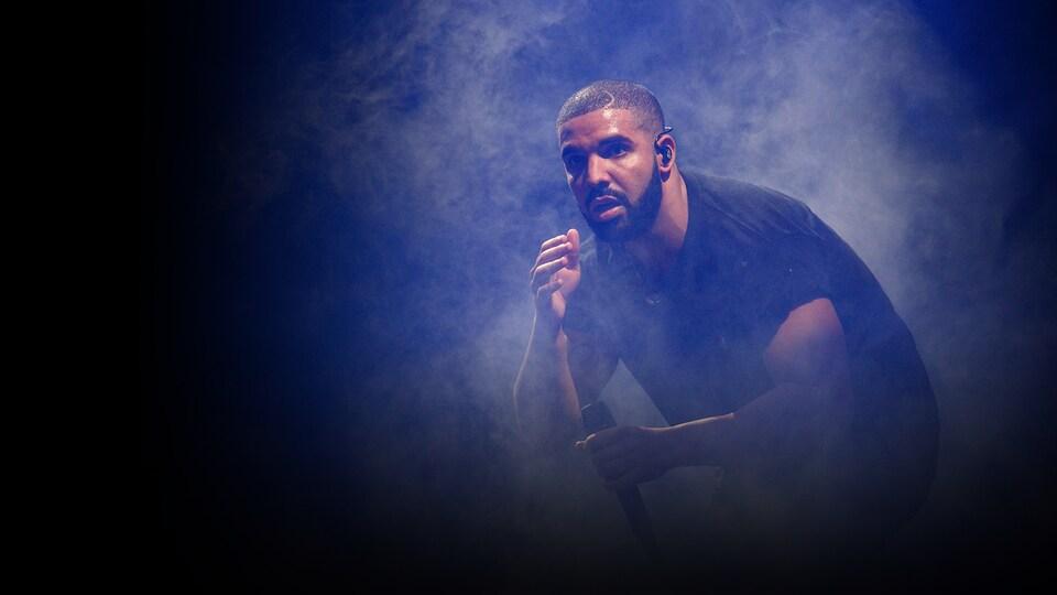 Un homme est accroupi dans le noir, sur une scène