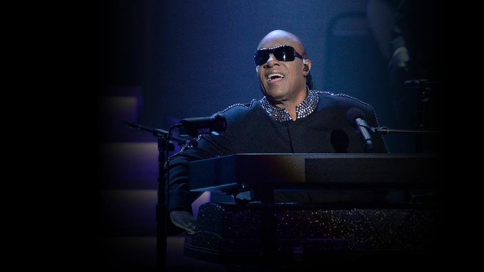 Un homme avec des lunettes fumées joue du piano sur scène.