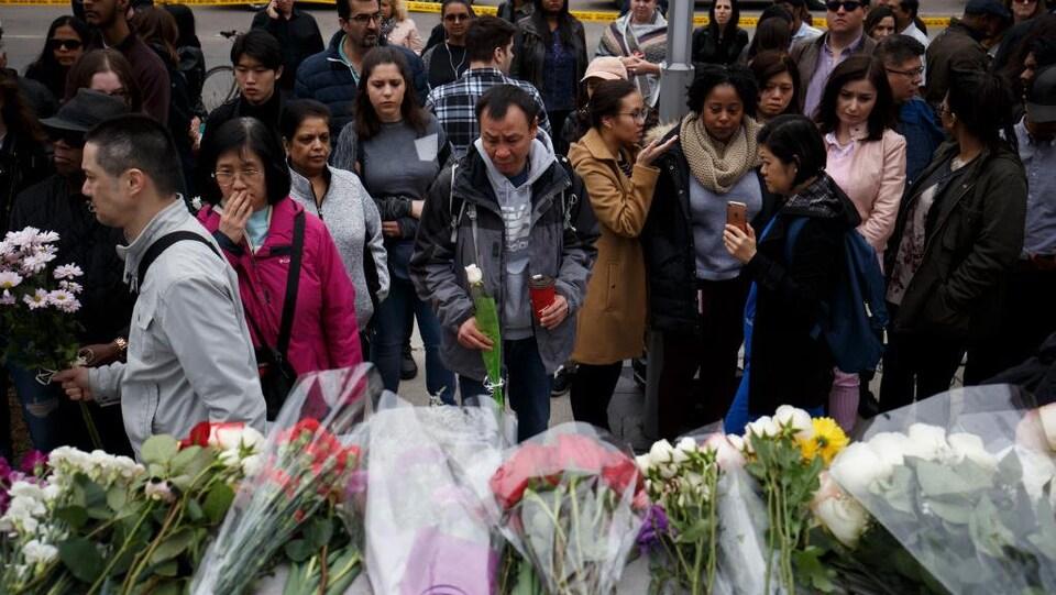 Des gens rassemblés devant des fleurs se recueillent.