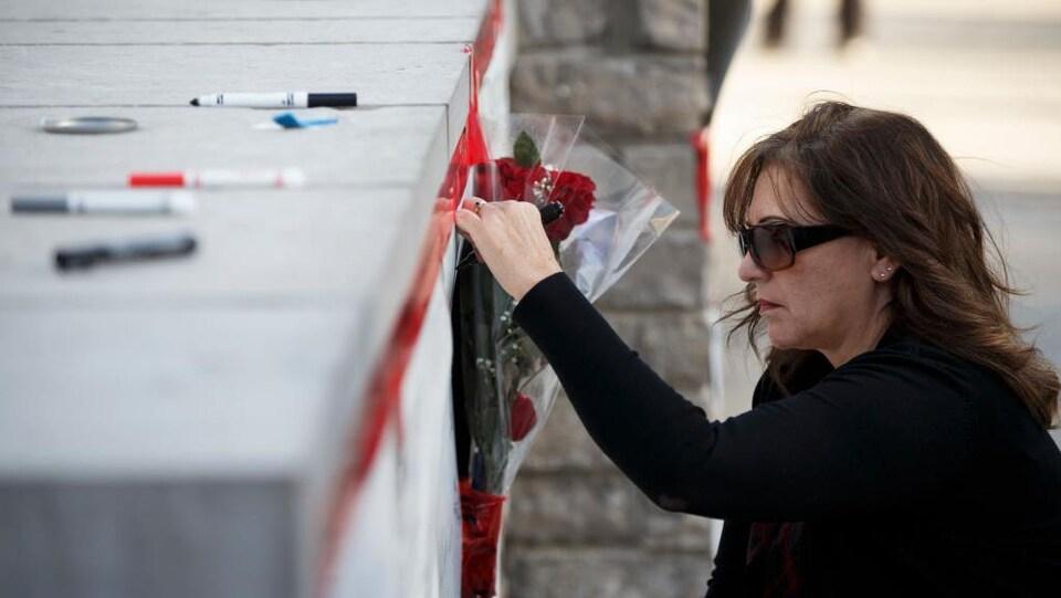 Une femme dépose une fleur sur un petit monument.