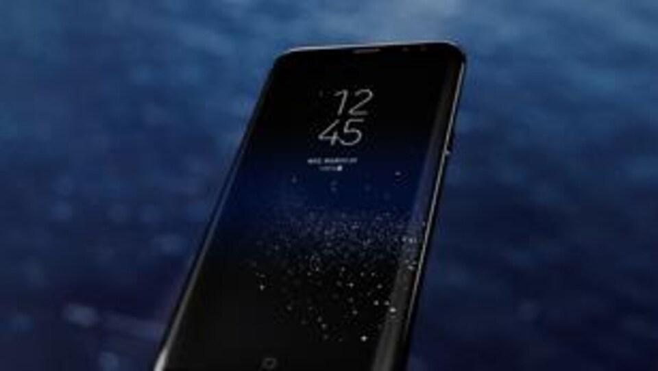 Un téléphone Samsung Galaxy S8 en veille sur un fond sombre.