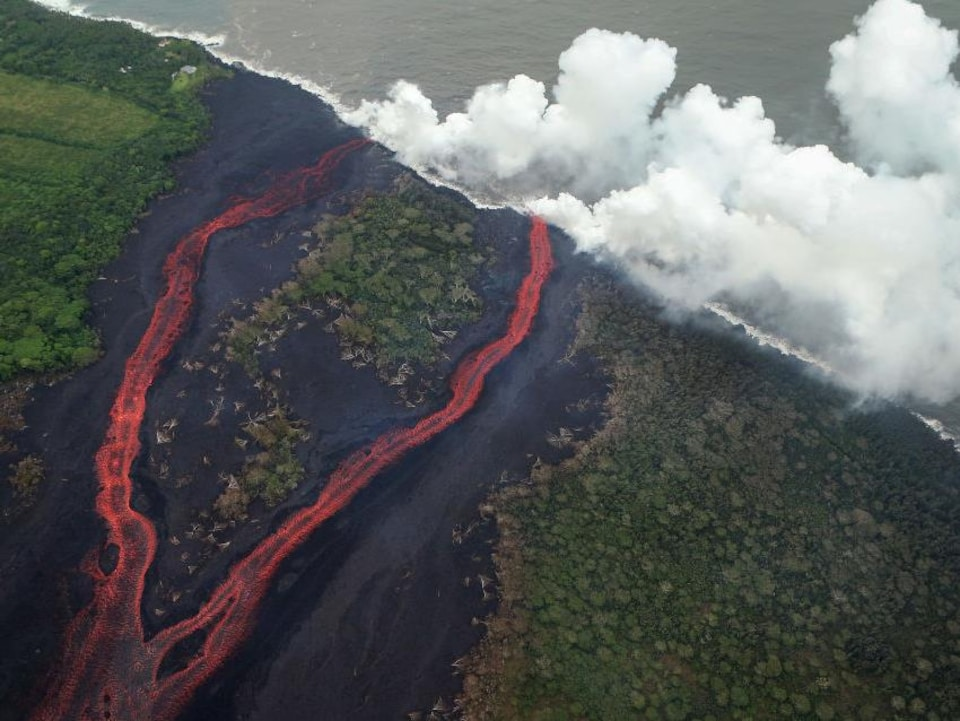 PAHOA, HI - MAY 21:  Steam plumes rise as lava enters the Pacific Ocean, after flowing to the water from a Kilauea volcano fissure, on Hawaii's Big Island on May 21, 2018 near Pahoa, Hawaii. Officials are concerned that 'laze', a dangerous product produced when hot lava hits cool ocean water, will affect residents. Laze, a word combination of lava and haze, contains hydrochloric acid steam along with volcanic glass particles.  (Photo by Mario Tama/Getty Images)
