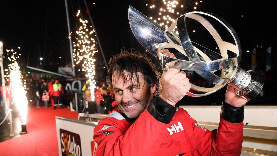 Il tient le trophée au-dessus de sa tête.