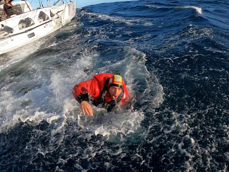 Kevin Escoffier quitte le bateau de Jean Le Cam après son sauvetage.