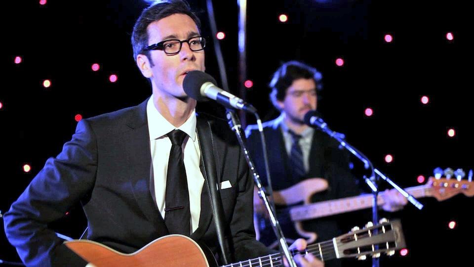 David Myles sur scène chantant une guitare à la main.