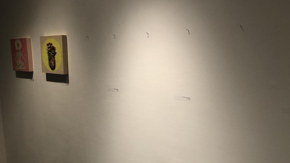 Sur un mur, deux toiles, et trois crochets où étaient auparavant accrochées trois toiles.