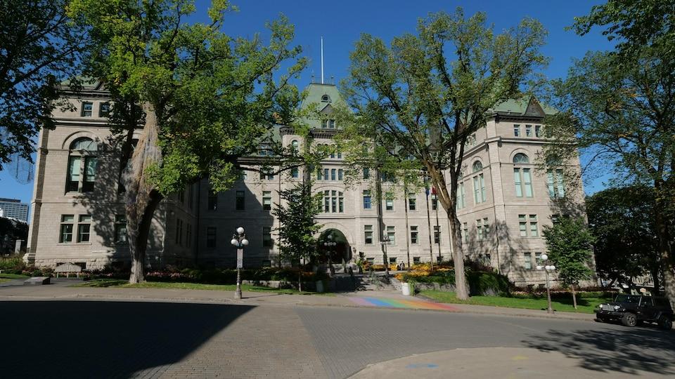 La façade ensoleillée de l'hôtel de ville de Québec, avec ses ormes majestueux.