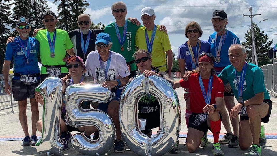 Une dizaine de personnes venant de terminer une course posent avec des ballons indiquant 150.