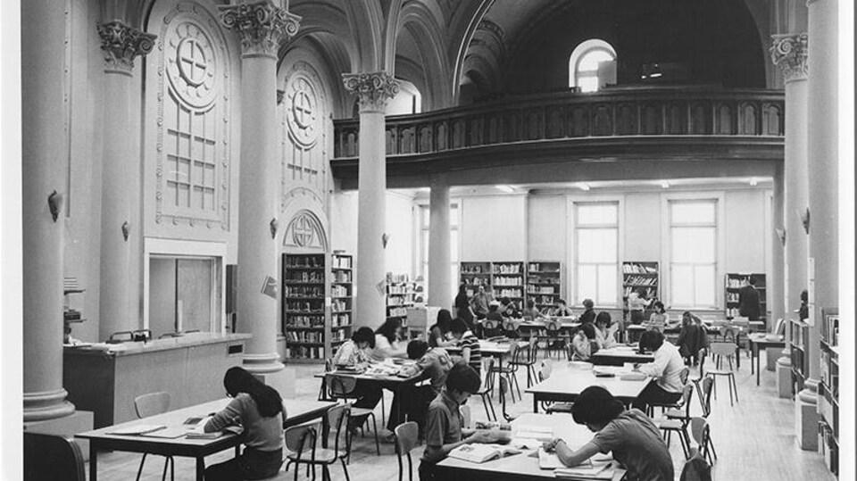 Vue en plan large d'une grande salle avec des tables où des étudiants sont au travail. Des étagères avec des livres meublent certains des murs qui les entourent.