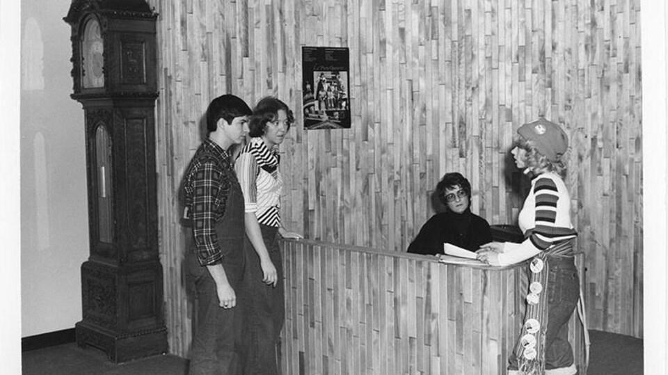 Quatre personnes, trois étudiants et une réceptionniste sont autour de la réception. Les murs sont faits de lattes de bois. À la gauche, il y a une grande horloge grand-père.