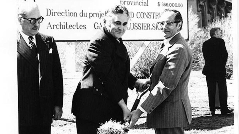 À l'avant-plan, trois hommes sont debout et deux d'entre eux tiennent une pelle en regardant le photographe et en souriant, devant un édifice et une grande affiche qui détaille les éléments du projet de construction.