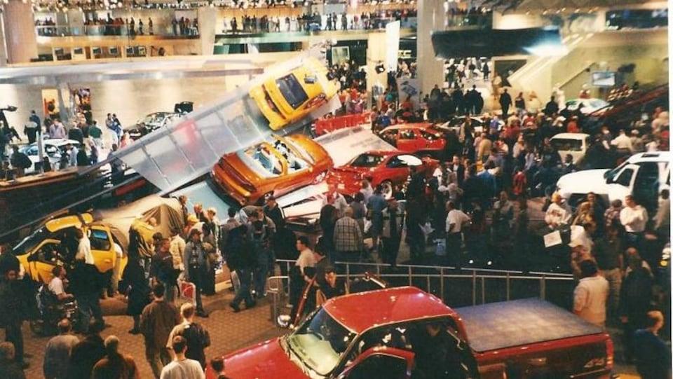 Des centaines de personnes sont au salon de l'auto, qui montre surtout des voitures dans les tons de rouge, d'oranger et de blanc.
