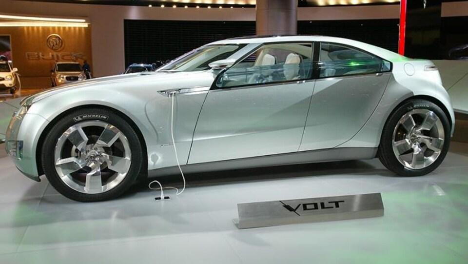 Une voiture électrique, branché au sol, le véhicule est argenté et on ne voit personne dans la photo