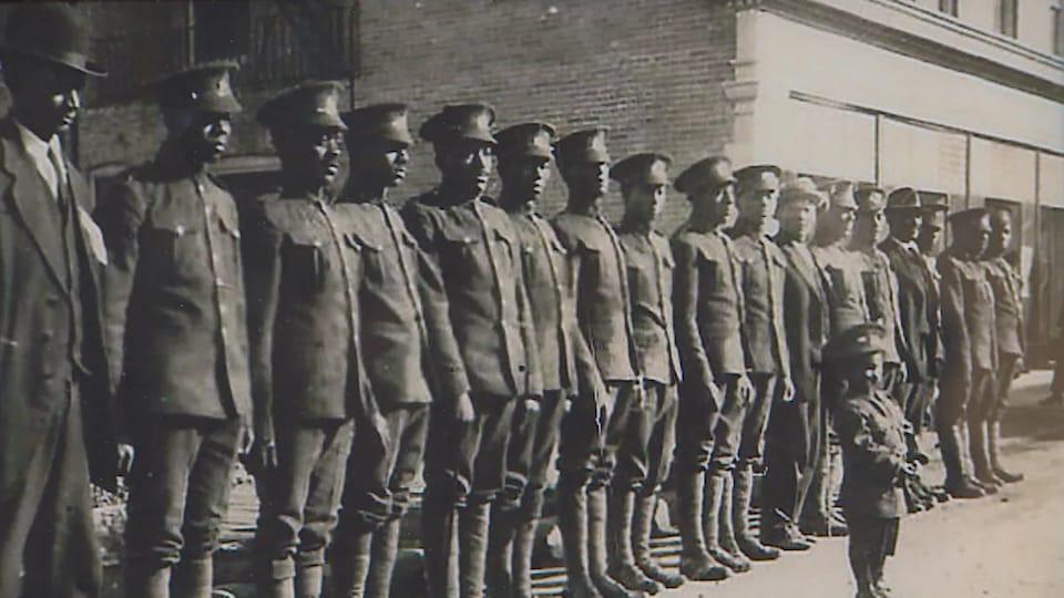 Des soldats au garde-à-vous, en uniforme, mais sans arme.