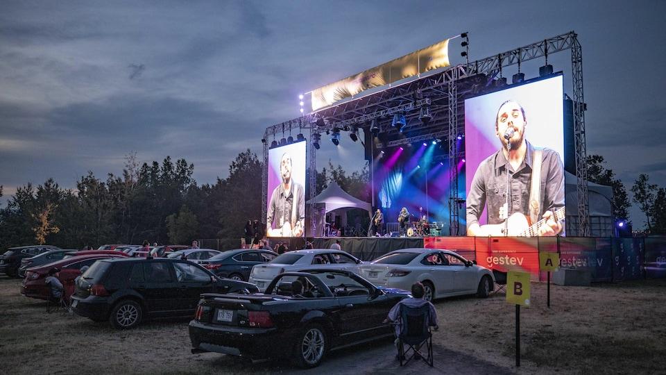 Le groupe 2Frères jouent sur une scène devant des voitures.