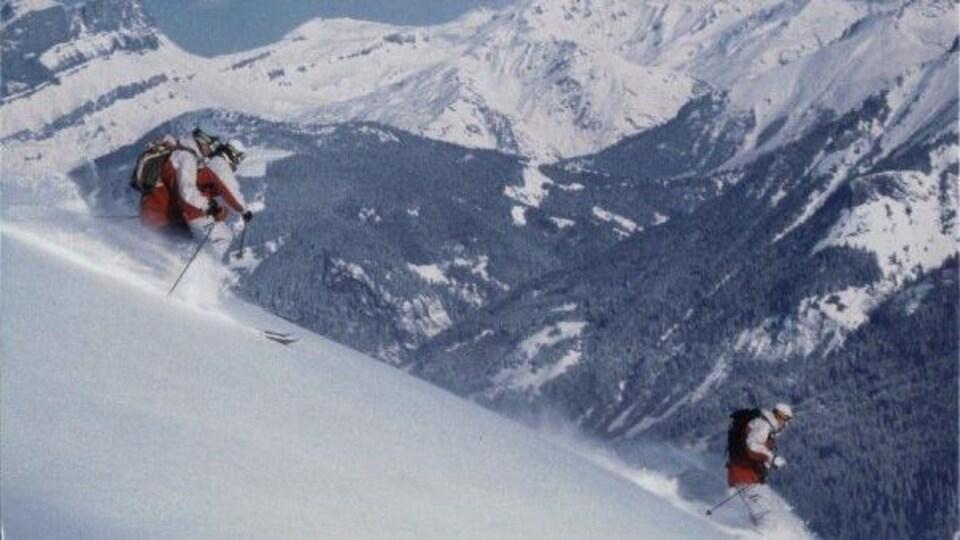 Trois skieurs dévalent une pente