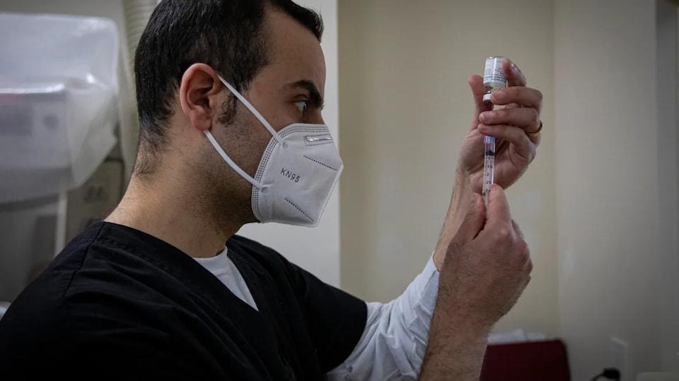 Membre du personnel médical préparant une dose de vaccin.