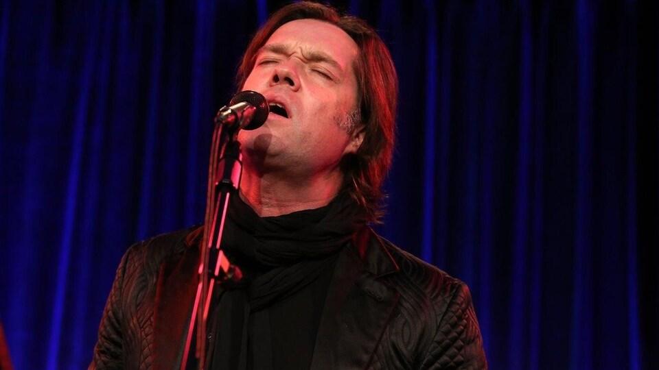 Le chanteur ferme les yeux et chante.