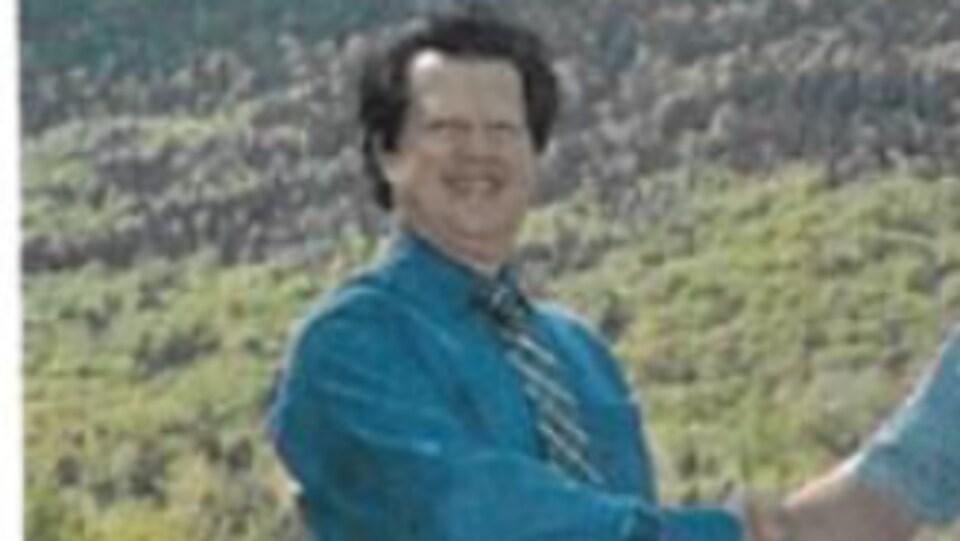 Un  homme en chemise cravate serre une main devant une forêt.