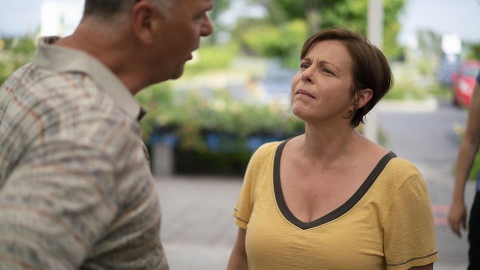 Une femme, portant un T-shirt jaune, regarde un homme.