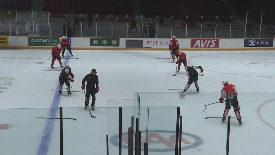 Des joueurs de hockey font passer une rondelle autour d'un bâton.