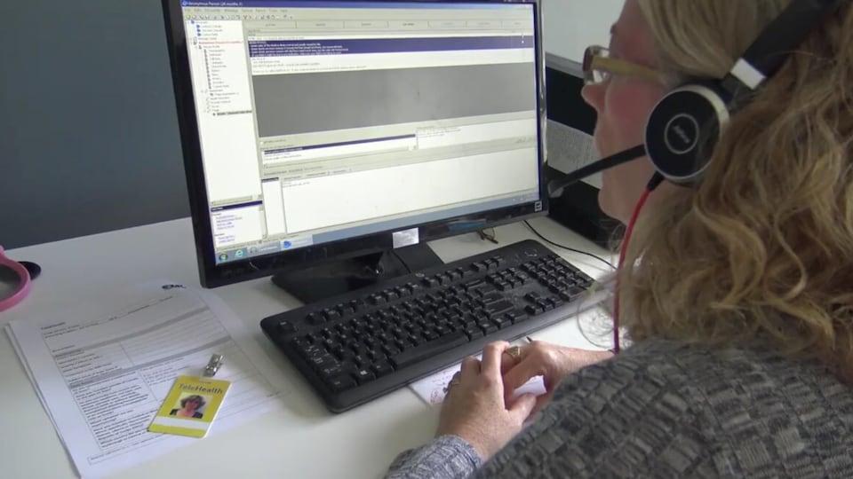 Une femme travaillant à un ordinateur porte un casque muni d'un micro pour répondre aux appels du public.