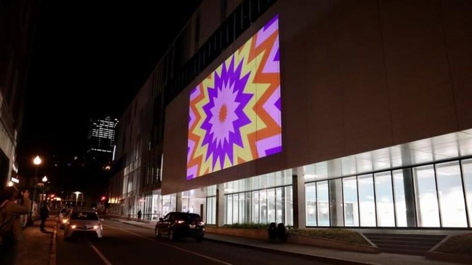 Une projection colorée sur un mur d'un grand bâtiment qui longe une rue, la nuit.