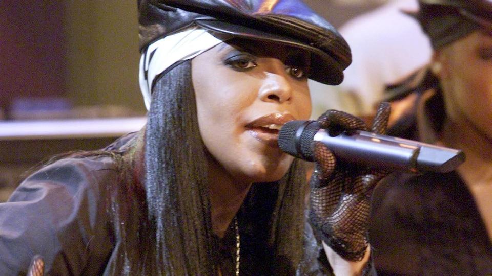 La jeune femme porte une casquette noire et chante dans un micro.