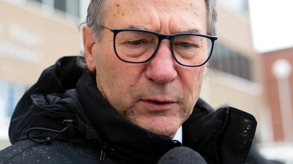 Aaron Fox porte des lunettes noires et répond à une question d'un journaliste devant la cour à Regina.