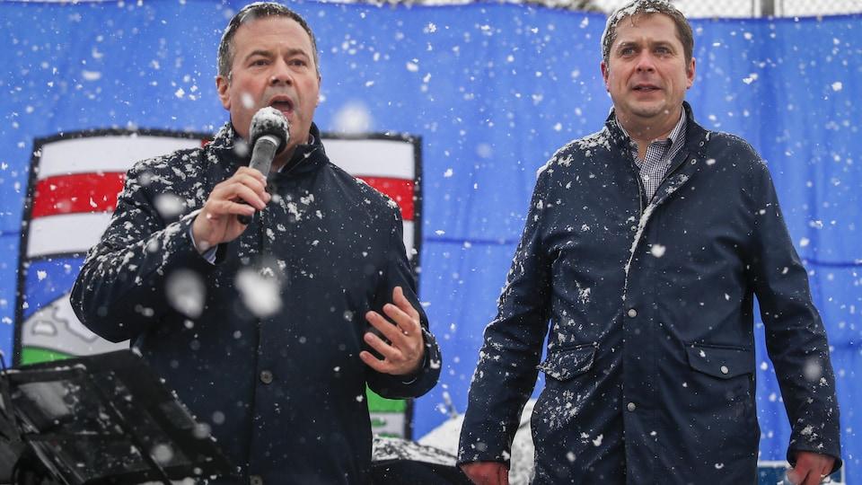 Sous la tempête hivernale, Jason Kenney et Andrew Scheer se rallient sur une estrade.