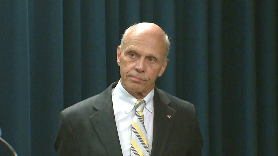 Steve Allan, en conférence de presse devant un rideau noir.
