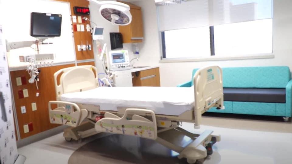 Une chambre de soins intensifs munie d'un canapé, d'un lit d'hôpital et d'équipement médical.