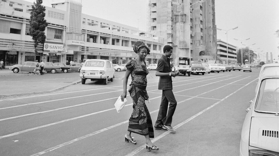 Un homme habillé en abacost et une femme habillée en pagne traversent le boulevard du 30 juin  à Kinshasa