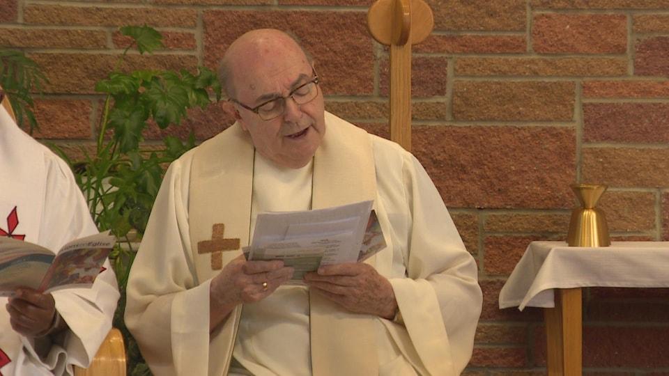 L'abbé Bernard de Margerie le regard porter sur un feuillet de prières.