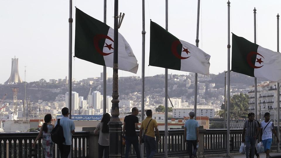 À Alger, des passants croisent des drapeaux de l'Algérie qui sont en berne.