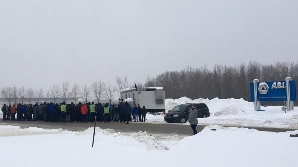 Des travailleurs sont regroupés devant une roulotte installée par le syndicat.