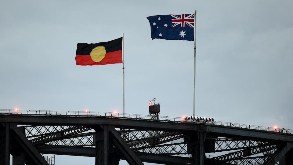 Deux drapeaux flottent au-dessus d'un pont par une journée ennuagée.