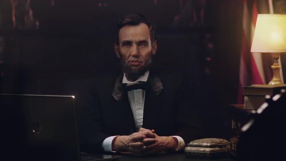 Abraham Lincoln, assis devant un bureau avec un ordinateur et une lampe.