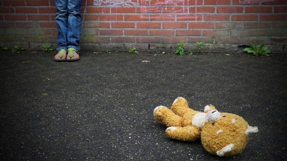 Un toutou repose au sol devant un enfant que l'on voit partiellement.