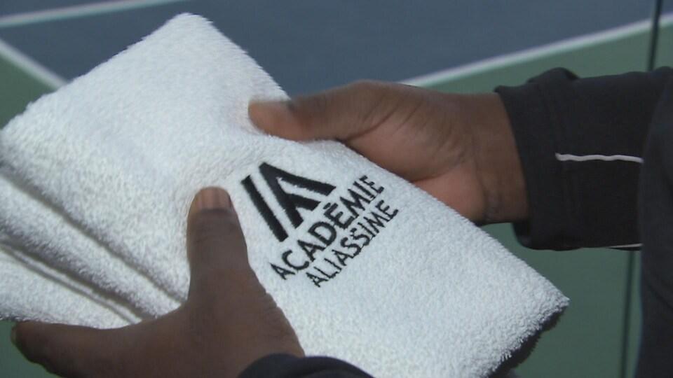 Un serviette avec un logo de l'Académie Aliassime