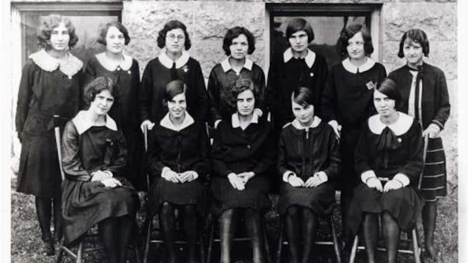 Une photo en noir et blanc d'une classe de jeunes filles, vêtues d'uniformes foncés.
