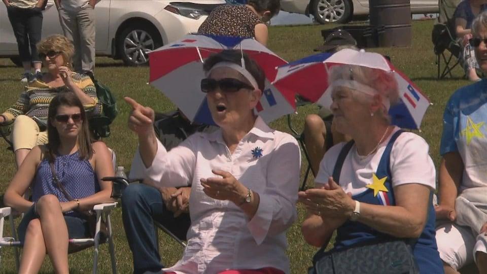Des dames âgées sont habillées aux couleurs de l'Acadie et ont beaucoup de plaisir à regarder le spectacle.