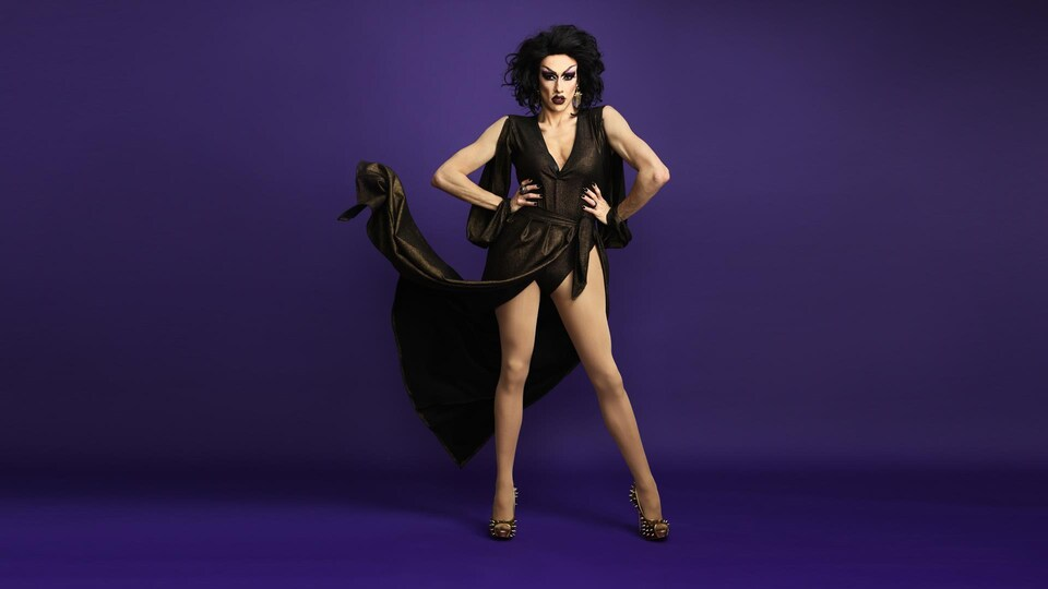 Une drag queen aux cheveux bouclés noirs porte une robe avec une fente jusqu'à la taille qui laisse paraître ses jambes nues. Elle regarde la caméra avec les mains sur les hanches et sa robe flotte près de son coude droit.