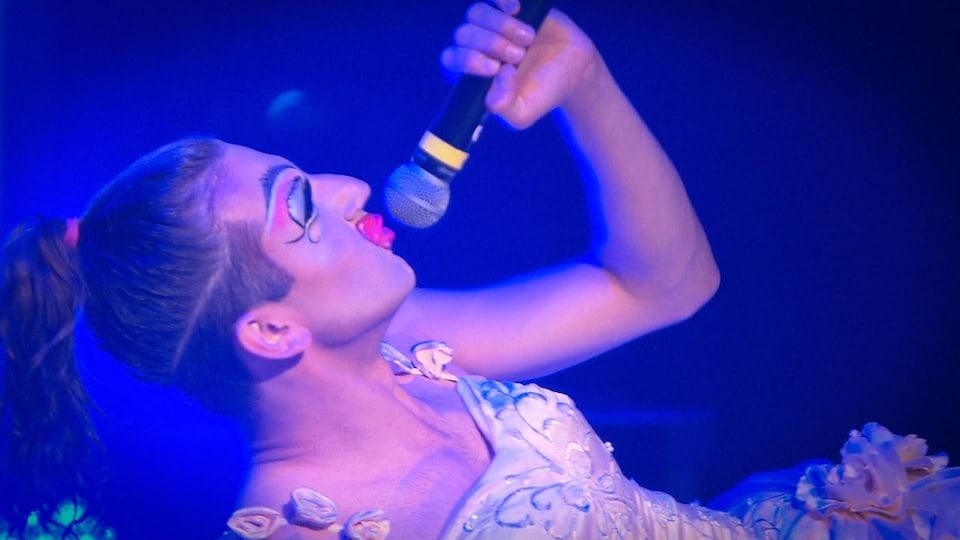Chiquita Mare, vêtue d'une robe blanche, est allongée sur le dos et parle dans un micro lors du spectacle.